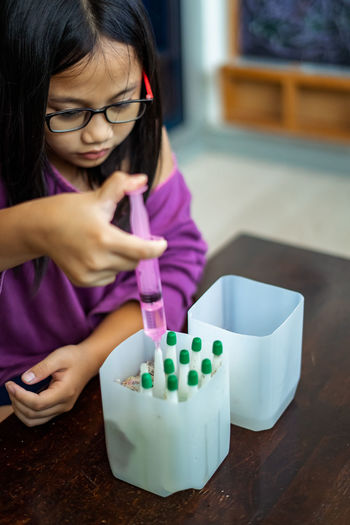 Child injecting organic fertilizer into small containers to be placed into the plant soil.