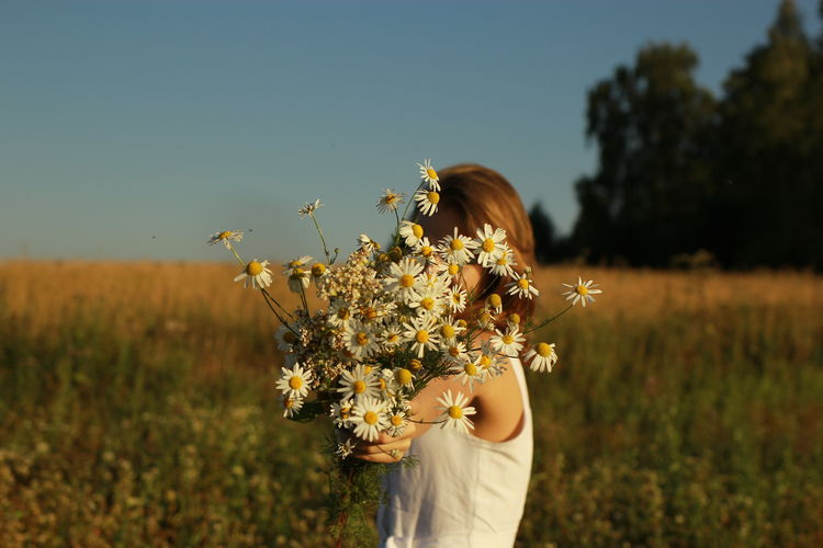 Midsection of woman holding sunflower on field against sky
