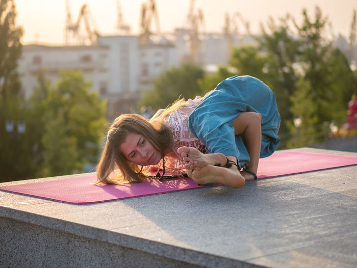 Young Woman Exercising On Exercise Mat During Sunset