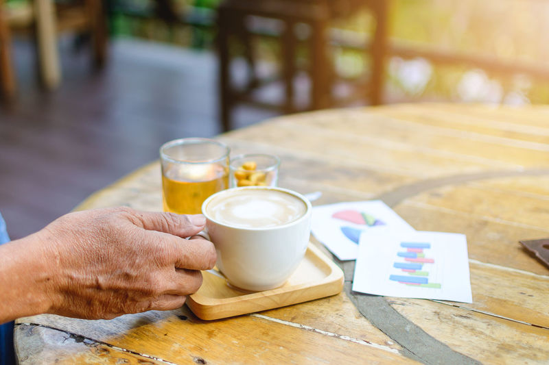 Cropped hands of man holding coffee cup on table at cafe