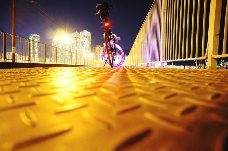 Surface level of bicycle against illuminated city at night