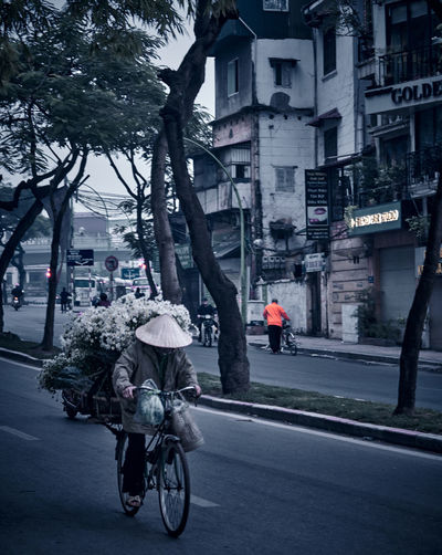 Rear view of man riding bicycle on street against buildings