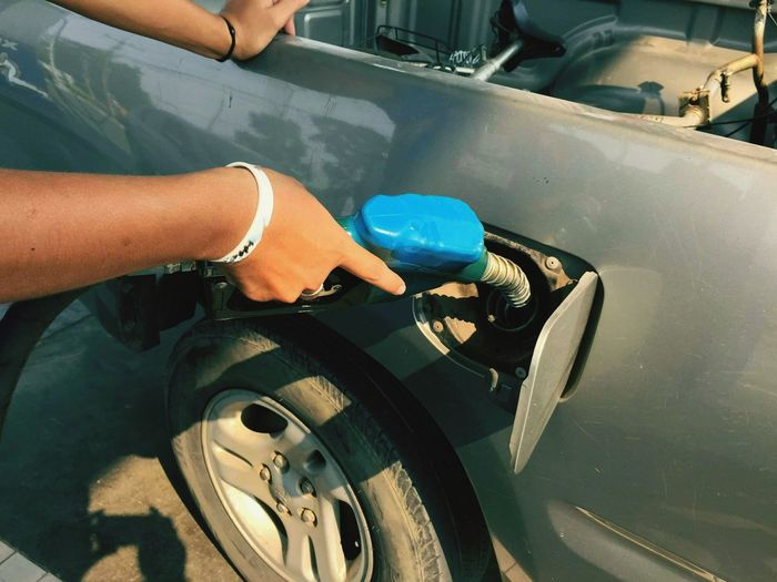 Closeup hand pumping Fuel nozzle gasoline fuel in white car at gas station Human Hand Car Wash Occupation Cleaning Industry Car Fuel Pump Washing Close-up