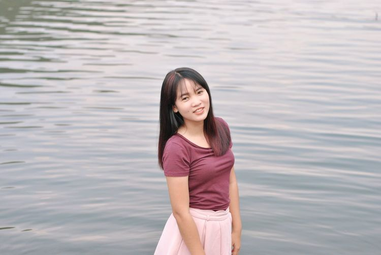 Portrait of smiling young woman standing in water