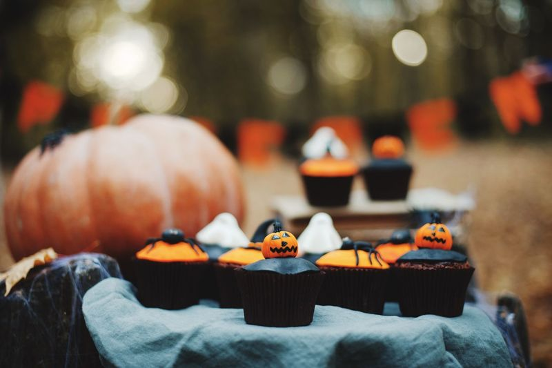 Close-up of cupcakes and pumpkin on table during halloween celebration