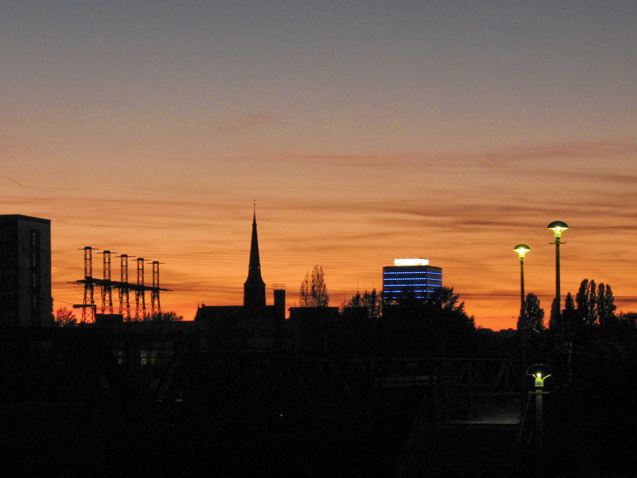sunset, building exterior, architecture, built structure, silhouette, orange color, tower, city, copy space, sky, communications tower, clear sky, dusk, tall - high, spire, outdoors, street light, no people, cityscape, building