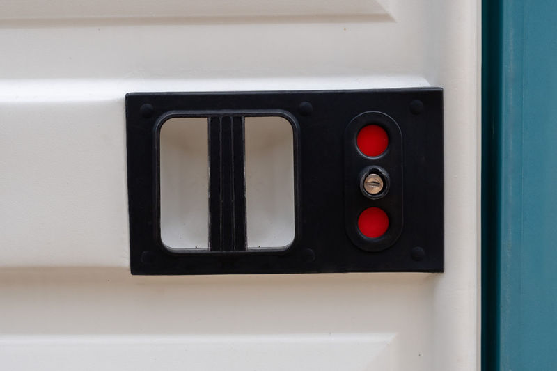 Close-up of a portable toilet door lock with red sign Bio Toilet Biological Black Color Close-up Control Electrical Equipment Geometric Shape Guidance Illuminated Indoors  Industry No People Portable Red Safety Security Shape Sign Technology Wc White Color