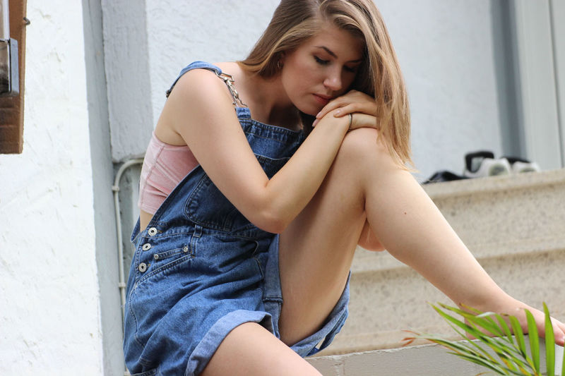 Young Woman In Bib Overalls Sitting On Retaining Wall