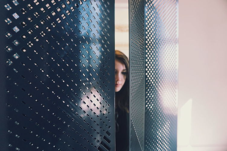 Close-up of young woman seen through metal