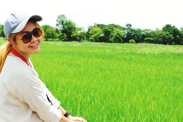 Portrait of smiling woman wearing sunglasses by rice field