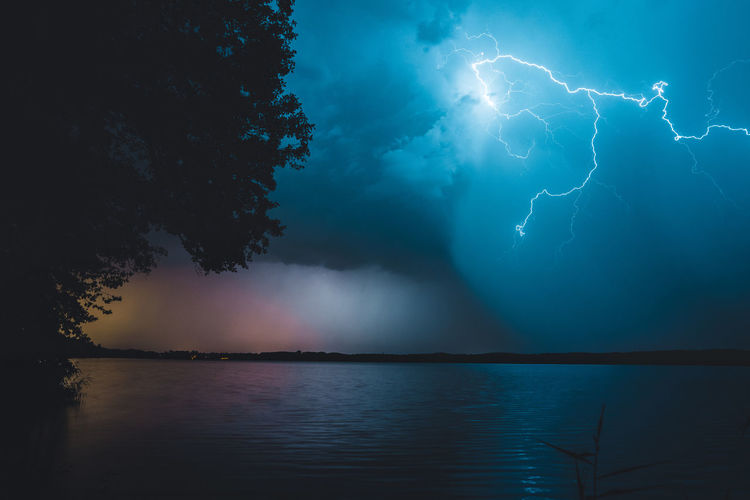 Beauty In Nature Cloud - Sky Forked Lightning Lake Lightning Nature No People Outdoors Power Power In Nature Reflection Scenics - Nature Sky Storm Storm Cloud Thunderstorm Tree Water