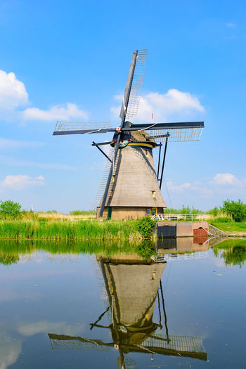Traditional windmill on lake against sky