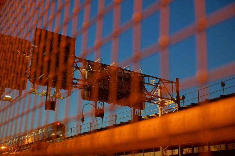 Railway bridge seen through metal grate at night
