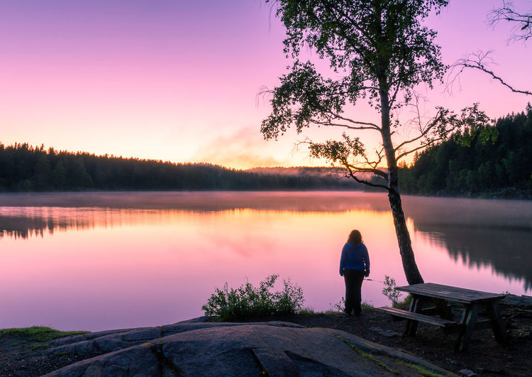Rear View Of Woman Standing At Lake Against Sky During Sunset