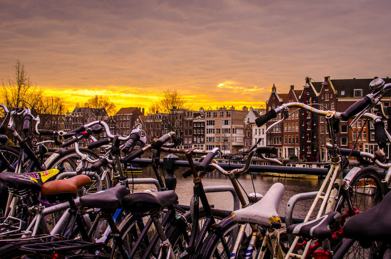 Bicycles in city against sky during sunset
