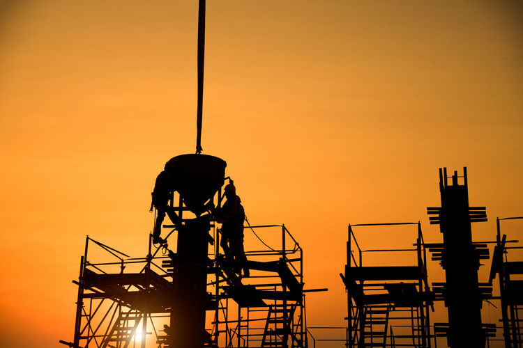 Low angle view of silhouette man standing against orange sky