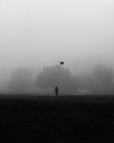 Silhouette person on field against sky