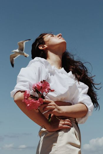 Low angle view of woman holding flowering plant against sky