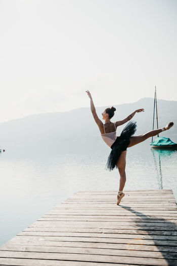 Ballet dancer dancing on pier over lake against mountains