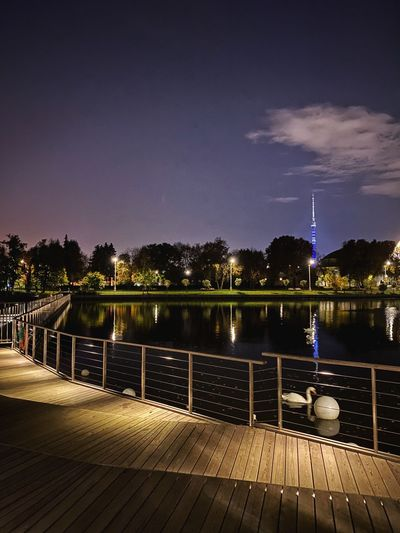 Pier over lake against sky at night