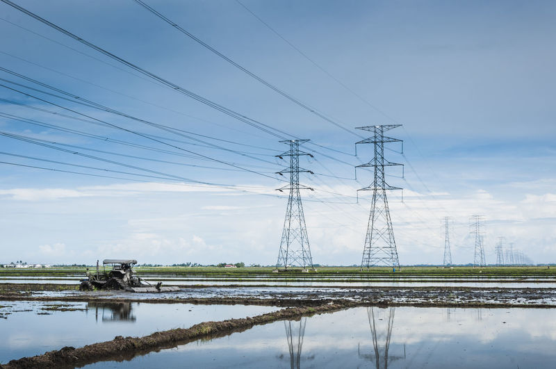 Electricity pylons at farm field against sky