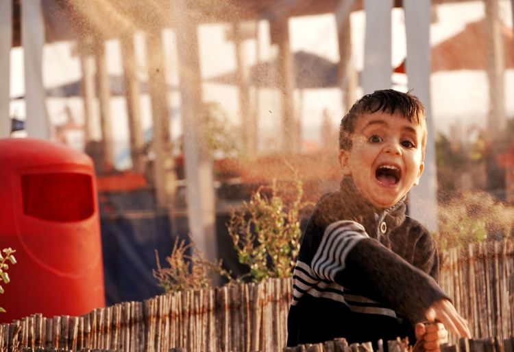 Portrait of happy boy throwing dirt outdoors