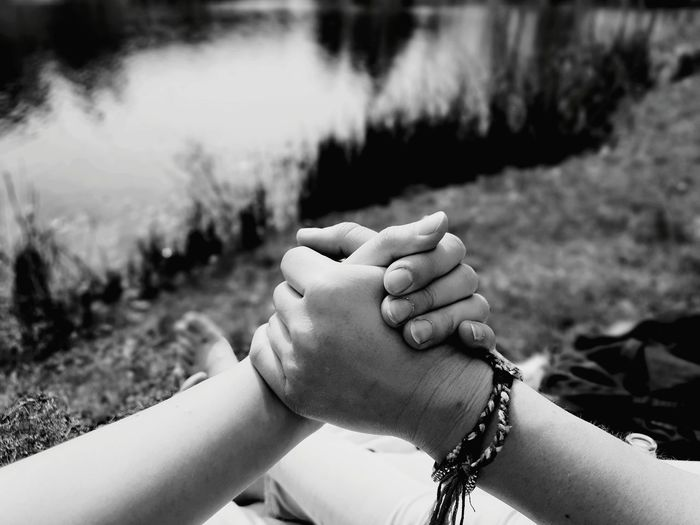 Cropped image of friends holding hands on field