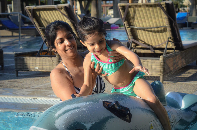 Mother and daughter in swimming pool. Family Fun Holiday Indian Mother And Daughter Swimming British Holiday Maker Day Time Female Girl Outdoors Pool Pool Toys School Age Single Mother Springtime Summer Swimming Pool Toddler  Two People Vacation