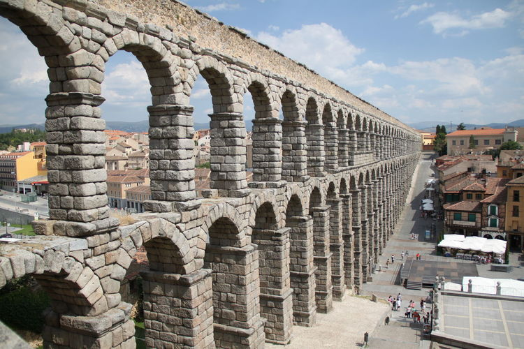 Roman aqueduct by buildings in city
