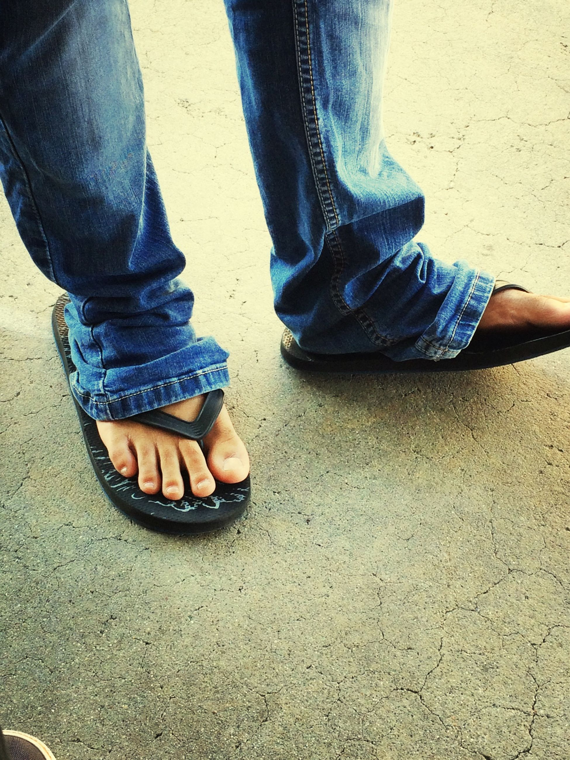 low section, person, shoe, jeans, standing, footwear, human foot, lifestyles, men, casual clothing, leisure activity, canvas shoe, fashion, denim, street