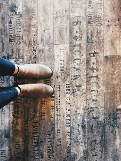 Low section of woman with text on wooden planks