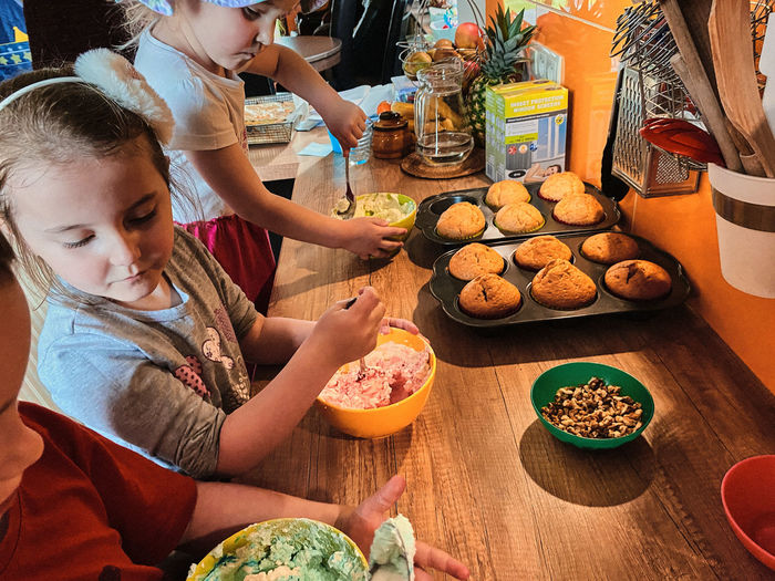 Group of children baking cupcakes, preparing ingredients, toppings, sprinkles for decorating cookies