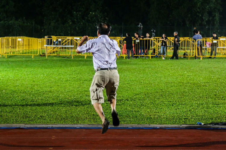 Rear View Of Man Jumping On Field In City During Election At Night