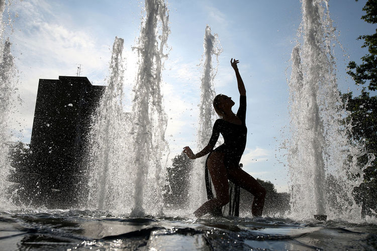 Silhouette woman splashing water fountain against sky