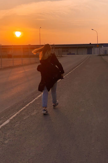 Rear view of woman standing on street against orange sky