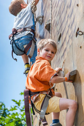 Portrait of boy with brother climbing wall