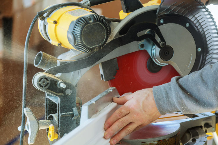 Cropped hand cutting metal with electric saw in workshop