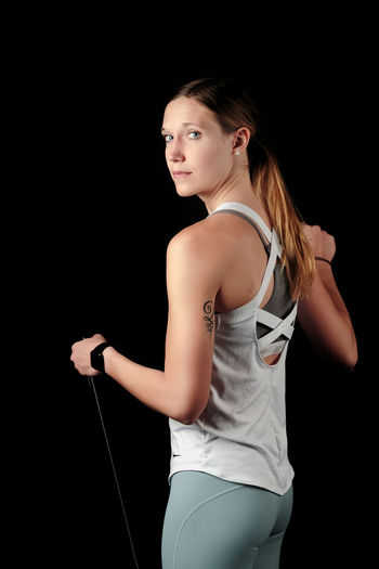Young woman looking away while standing against black background Adult Sport Activity Athletic Attractive Beautiful Body Exercise Female Fit Fitness Girl Gym Health Healthy Lifestyle Muscle One person Pilates Pose Slim Sportswear Studio Training Weight Wellness Woman Workout Young Three Quarter Length Black Background One Person Studio Shot Young Women Standing Young Adult Lifestyles Women Indoors  Clothing Beauty Sports Clothing Hairstyle Beautiful Woman Cut Out Hair