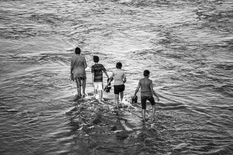 Kids having fun in the river. Beach Black And White Boys Child Childhood Day India Kids Kids Being Kids Kids Having Fun Kids Playing Kidsphotography Men Monochrome Monochrome Photography My Year My View Nature Outdoors People Real People Sea Summer Togetherness Water Wave Flying High Welcome To Black Resist The Great Outdoors - 2017 EyeEm Awards Black And White Friday Go Higher A New Beginning