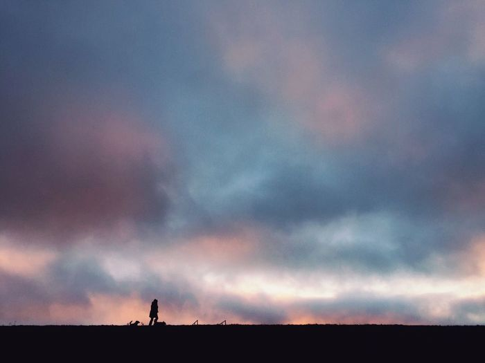 Silhouette woman with dog walking against cloudy sky at dusk