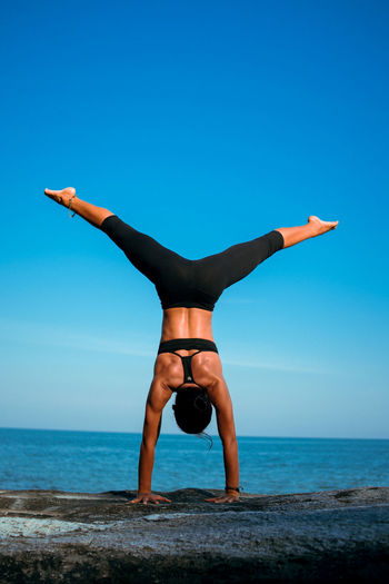 Full length of woman exercising at beach against clear blue sky