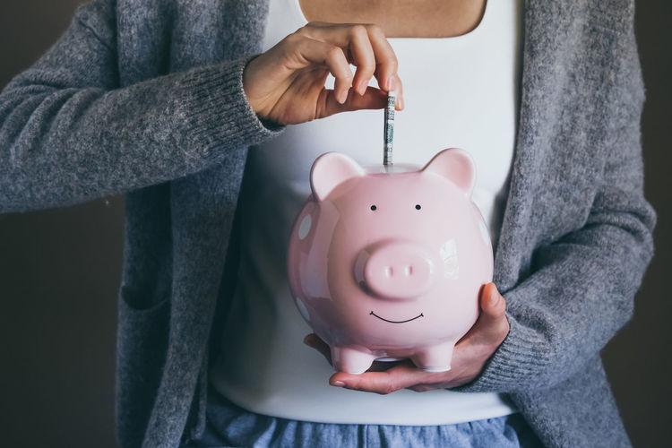 Woman putting bill in piggy bank. saving money. economic crisis