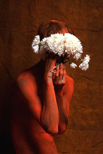 Man with flowers standing against wall