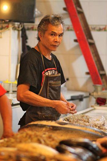 Portrait Of Chef Making Seafood In Commercial Kitchen