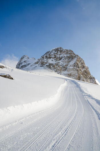 Beauty In Nature Clear Sky Cold Temperature Day Landscape Mountain Nature No People Outdoors Scenics Sky Snow The Way Forward Tire Track Track - Imprint Tranquil Scene Tranquility Winter
