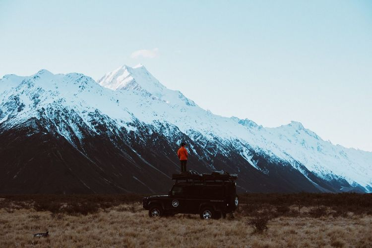 Person Standing On Top Of Car Against Snowcapped Mountains