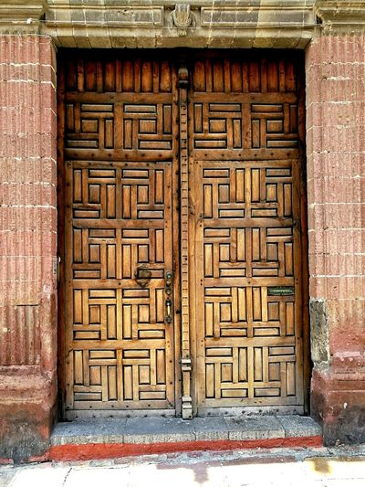 Stylish carved wooden door design, front of a building entrance, Mexico Front View Carpentry Security Closed Locked Portal Gate Fancy Old Carved Engraved Carving Wooden Brown Bricks Doorway Frame Stylish Mexico Entrance Building Door Façade Entry Textured  Pattern Door Safety Wood - Material Entrance