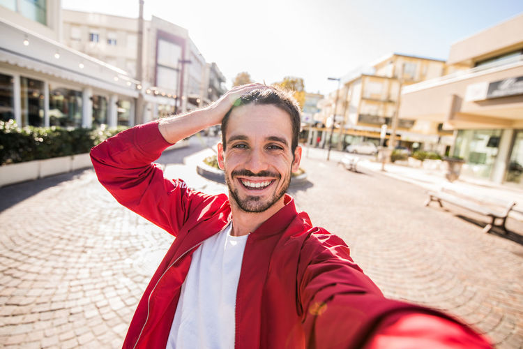 Portrait of smiling man with hand in hair standing in city