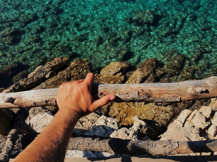 Cropped hand holding wooden railing