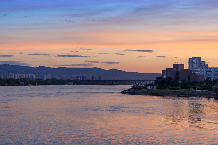 Sunset over Yenisei river in Krasnoyarsk city. River Collection River View Riverside Yenisei River Architecture Building Building Exterior Built Structure City Cityscape Cloud - Sky No People Orange Color Outdoors River Riverbank Riverscape Siberia Sky Sunset Water Waterfront